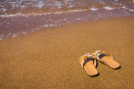 Sea coast, wet sand, clear water. On the shore there are summer female slippers. Bright sunny day, heat. Imagens - 122434244