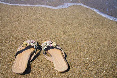 Summer, sea coast, clear water. On the sand female slippers. Single trip, vacation, downshifting. Bright solar lighting. Imagens - 122434246