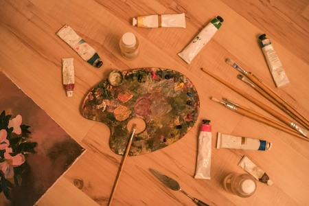 Oil paints in tubes, brushes, canvas, palette knife, palette for mixing paints. Drawing, creativity, hobby. Wooden background, top view.