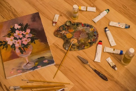 Painting supplies, canvas with still life. Drawing from nature, creativity, art. Brushes, paint and palette on wooden background.