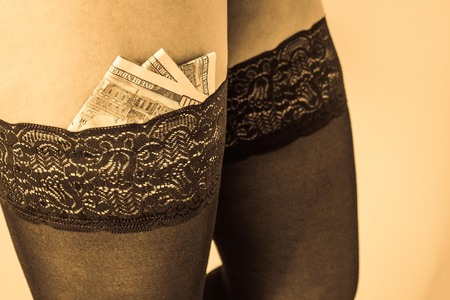 Money inserted into the lace gum stocking. Sex industry, selling love, crime, pimping. Muted tones, vintage toning.