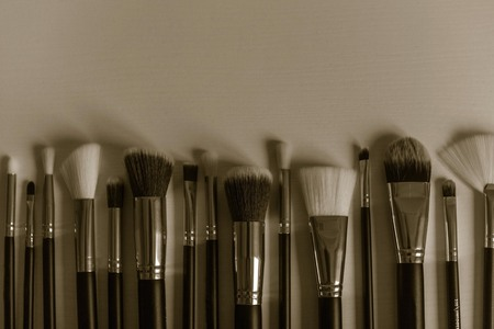 A set of brushes for makeup, different types, shapes, sizes. Profession makeup artist, creating a new image. Muffled tones, copy space. Imagens