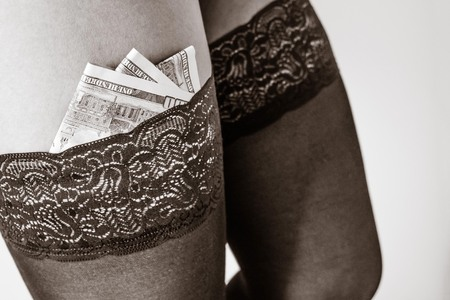 The girl has stocked dollars in stockings. Payment for sexual services. Prostitution, sales feelings. In black and white. Imagens - 122434363
