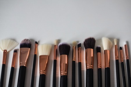 Profession makeup artist, beauty art, creating a new image. Brushes of different sizes, choice, alternative. Light background, copy space.