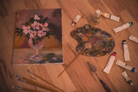 Art supplies, brushes and oil paints. Painting, creativity, hobby. wooden surface, vignetting. Imagens