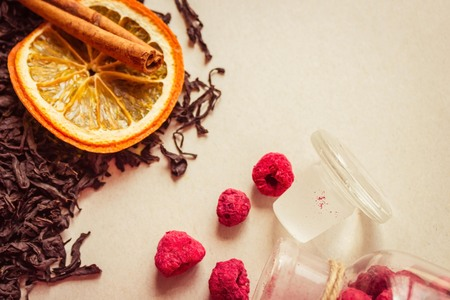 Dried raspberries, orange and cinnamon alongside the large dried leaves of the tea tree. Fermented tea, collection grade. Light background, copy space, top view.