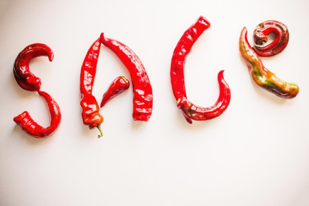 Letters from pods of hot pepper, bright red color. The season of sales, discounts, hot prices. Light background, copy space. Imagens