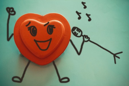 Red heart on a blue background. In the hands of the microphone. A joyful emotion, a bright expression of happiness. Figure made by the author.
