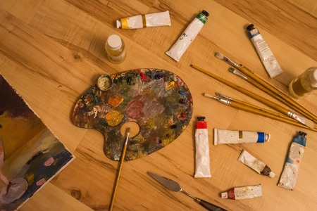 Artist's palette with oil paints, brushes of different sizes, oil paints in tubes. Oil painting, art, creative talent. Top view, vignetting. Imagens - 122434416