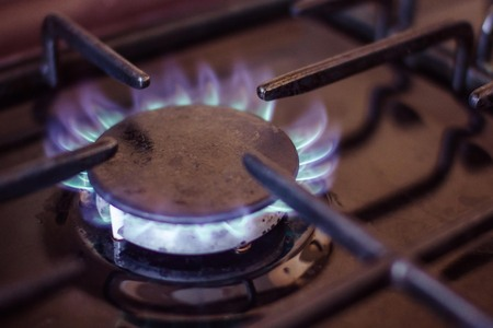 Gas stove, lit burner. Extraction and use of natural gas. Blue flame on a dark background, the edges are blurred.