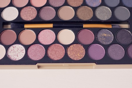 Creating a new image, bright makeup, the use of decorative cosmetics. Room for creativity. Palette with eyeshadow and brush. View from above.