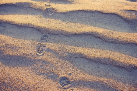 Footprints in the sand, return. Road as a lifestyle. Homecoming. Lateral sunlight, evening.