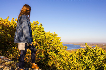 The girl looks from the cliff to the river, landscape. Active lifestyle, modern youth clothing. Clear cloudless sky, bright colors, early autumn. View from the back.