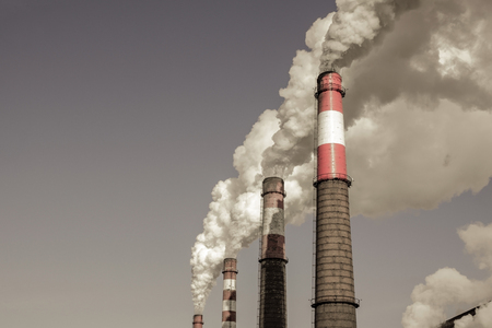 Pipes smoke in the sky, environmental pollution. The impact of industry on the ecology. Muffled tones, copy space.