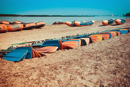 On the sandy shore boats and catamarans. In the foreground are many oars for rowing. Collective rest, river rafting, active lifestyle. Sunny summer day. Toning.