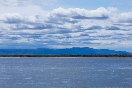 Summer landscape, wide river. In the distance the coast, the mountains, the horizon line. Beautiful view, blue tones. Imagens