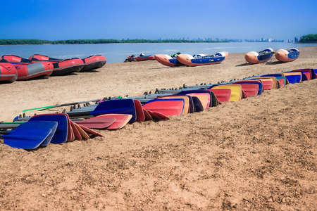 Rafts and oars on the bank near the river. Summer activity, team sport, rest. Blue sky, horizon. Sunny clear day.