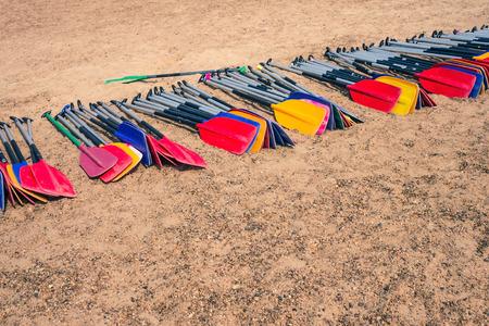 Paddles for rowing on the sand. Big team, teamwork, common goal, task. Rafting, summer activity. Solar lighting.