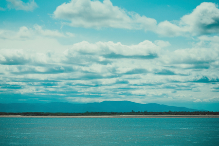 Beautiful summer landscape. River, sky, clouds, horizon line. Away blue hills. Solar lighting, summer day.