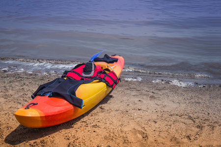 Kayak on the sandy shore. Blue water, river, sea. On top is sports equipment. Kayaking, water sports. Sunny summer day. Imagens