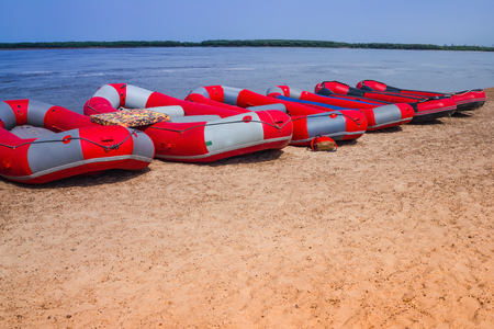 Blue river, sandy beach, hot summer day. The water has large inflatable boats, rafts. Water sports, active recreation. Toning.