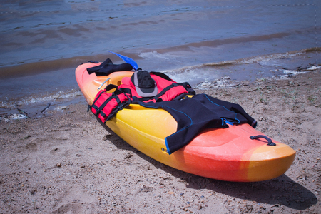 Active summer recreation on the water, kayaking. On the sand by the water is a kayak, on top of special equipment. Bright solar lighting, heat, summer. Imagens