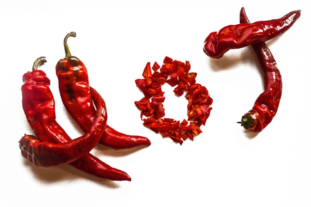 Spicy seasoning, piquant taste, peppercorn. The inscription is hot on a light background. Long pods of red pepper.