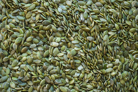 Background of green, small, peeled pumpkin seeds. A useful product in dietary nutrition, fasting. A natural source of vitamins. View from above. Imagens