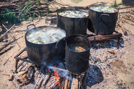 Cooking lunch in a hike, a fire on the sandy shore. Large pans with fish soup. Firewood, embers, bright fire. Hot sunny day, summer.
