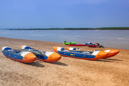 Activities on the river, water sports. Bright sunny day, the river bank, two catamarans. Blue water, horizon.