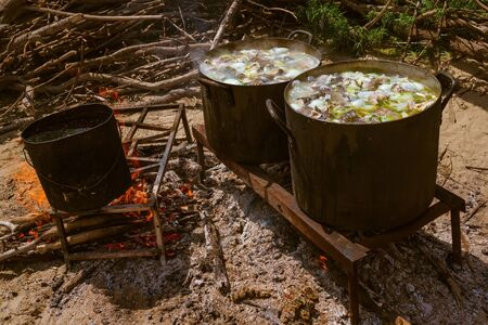 Cooking in nature, picnic, outdoor kitchen. Hot fish soup, simple tasty food. Bright fire, firewood, embers. Camping, hike. Sunny summer day. Imagens