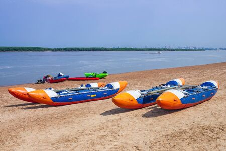 On the sandy shore are two catamarans. Activities on the river, sport. Summer, nature. Hot sunny day.