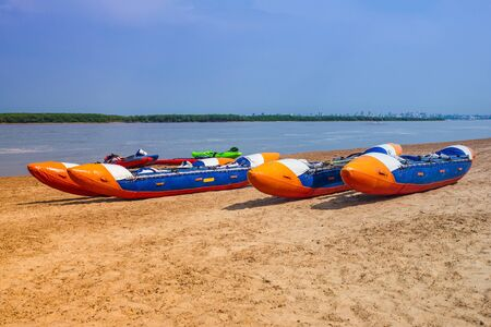Summer sunny day, blue river, yellow sandy shore. There are two inflatable catamarans near the water. Lifestyle, active recreation, water sports. Toning. Imagens