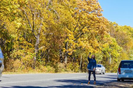 Young girl in denim clothes makes selfie on the road. Cars are driving by. Away yellow trees. Autumn, September, October. Clear sunny day.