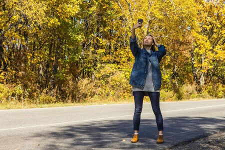 Selfie on a country highway. A young girl in denim clothes takes pictures on the phone. Modern fashion, casual style. In the distance, yellow forest trees.