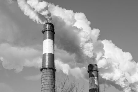 Smoking chimneys, thick puffs of white smoke. The impact of industry on the ecology, the problems of environmental pollution. In black and white, bottom view.