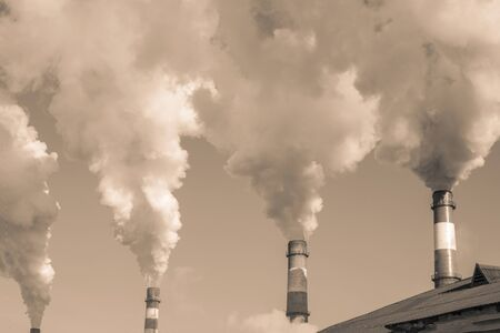Industrial pipes smoke against the sky. Global warming, environmental pollution, atmospheric emissions. Sepia.