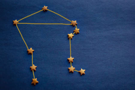 Constellation Libra, an astrological sign born in October. Gold stars on a blue background. Copy space, daylight. The picture is made by the author. Фото со стока