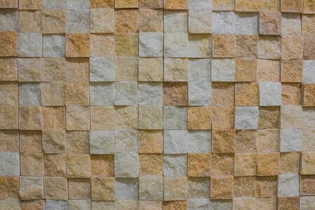 Wall, marble coating. Brown, orange and white cubes, abstraction. Interior decoration.