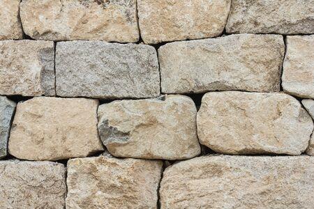Piedras grises en bruto, textura natural. Albañilería antigua, muralla, fortaleza. Foto de archivo