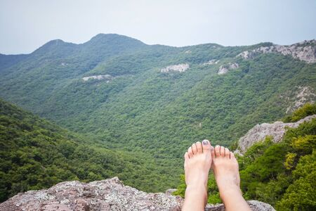 Female legs on a background of green mountains. Outdoor activities, hiking, travel. Summer day, cloudy. 写真素材