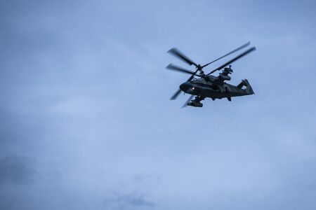 In a blue cloudy sky a military helicopter. Tactical exercises, maneuvers, aviation participation. Vignetting. Stock fotó