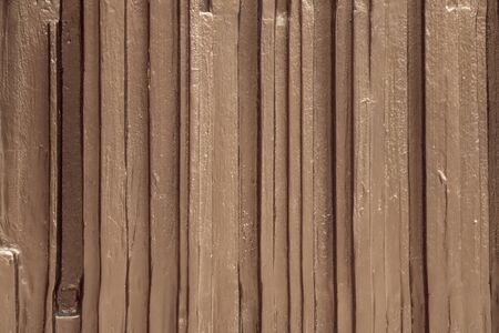 Abstract, neutral background with vertical stripes. Shallow relief. Golden color with a metallic sheen.