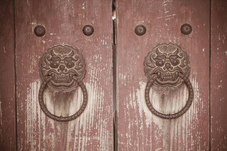 Vintage wooden door with iron handles. Shabby surface, cracks, peeling paint. South Korea, old Gyeongju. Vignetting.