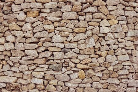 Old stone wall, masonry. Large rough stones of various sizes. Warm brown tones. 版權商用圖片