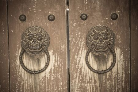 Silla Dynasty Palace in Gyeongju, ancient gate. Door handles in the form of the heads of demons, mythical creatures. Vintage toning, vignetting.