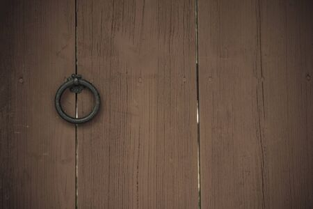 Old gates, wide planks, natural texture. Iron handle in the form of a ring. Locked door. Vintage style, vignetting.