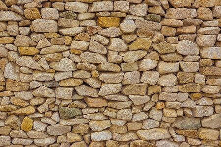 Old masonry made of stone. Reliable foundation. Rough natural stones, cobblestones. Warm brown tinting.