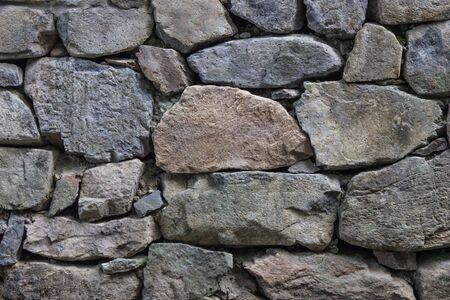 Large rough stones, natural texture. Ancient masonry, fortress wall. Cold gray shades.