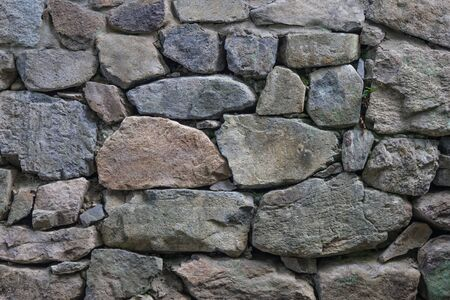 Huge natural stones of various shapes. Ancient masonry, foundation, fortress. Gray tones.